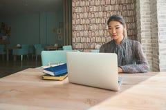 逗人喜爱的使用便携式计算机的妇女成功的自由职业者,当坐在咖啡店时 免版税库存照片