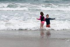 年轻逗人喜爱的使用在海边的小男孩和女孩遇到在一个沙滩的海浪在夏天阳光下 图库摄影