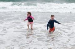 年轻逗人喜爱的使用在海边的小男孩和女孩遇到在一个沙滩的海浪在夏天阳光下 库存图片