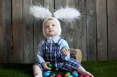 逗人喜爱的使用用复活节彩蛋的小孩男孩佩带的兔宝宝耳朵 免版税库存图片