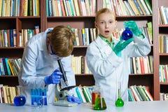 逗人喜爱的做生化研究的男孩和女孩  免版税图库摄影