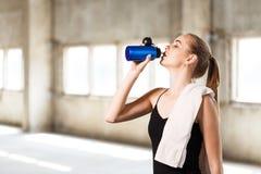 逗人喜爱的健身女孩放松的和饮用水 免版税库存照片