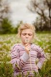 逗人喜爱的儿童吹的蒲公英花 免版税图库摄影