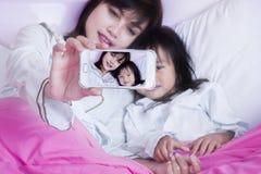 逗人喜爱的儿童和母亲作为selfie图片 免版税库存图片