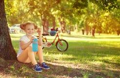 逗人喜爱的儿童女孩在手中坐在与瓶的树下 自行车 免版税图库摄影