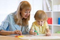逗人喜爱的儿童男孩图画和文字与五颜六色的记号笔在幼儿园 在playschool的创造性的孩子绘画 老师帮助 免版税库存照片