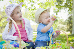 逗人喜爱的兄弟和姐妹享用复活节彩蛋外面 免版税库存照片