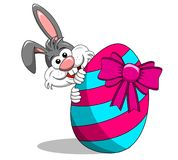 逗人喜爱的兔子或兔宝宝偷看在被绘的鸡蛋后的嘘与弓isol 免版税库存图片