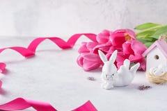 逗人喜爱的兔宝宝、桃红色郁金香、玩具房子和巢愉快的复活节卡片 免版税库存图片