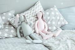 逗人喜爱的兔宝宝在床上戏弄在婴孩屋子里 免版税图库摄影