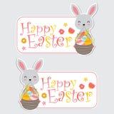 逗人喜爱的兔宝宝女孩和五颜六色的鸡蛋在篮子适用于愉快的复活节标签设计 图库摄影