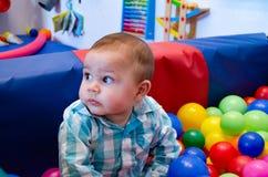 逗人喜爱的六个月使用与在育儿的五颜六色的球的男婴 免版税库存照片