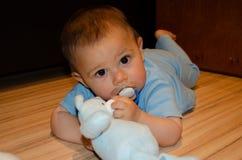 逗人喜爱的六个月使用与蓝色女用连杉衬裤的男婴涉及地板,长牙齿和早期的发展概念 免版税图库摄影