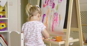 逗人喜爱的创造性的小女孩艺术家绘画 股票录像