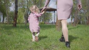 逗人喜爱的到处乱跑用藏品手的母亲和可爱的小女儿在惊人的绿色公园 妇女和孩子使用 股票录像