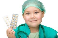 逗人喜爱的医生女孩一点药片使用 免版税库存图片