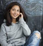 年轻逗人喜爱的十几岁的女孩在黑板就座的教室在桌微笑 免版税图库摄影