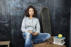 年轻逗人喜爱的十几岁的女孩在黑板就座的教室在桌微笑 免版税库存照片