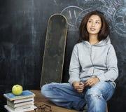 年轻逗人喜爱的十几岁的女孩在黑板就座的教室在桌微笑 库存照片