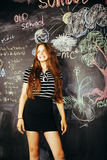 年轻逗人喜爱的十几岁的女孩在黑板愉快微笑的,教育人概念教室 免版税图库摄影