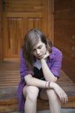 逗人喜爱的十几岁的女孩坐露天看台跨步与严肃的e 免版税图库摄影