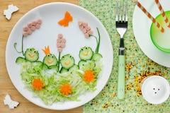 逗人喜爱的午餐想法:与滑稽的黄瓜青蛙的蔬菜沙拉 库存照片