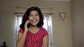 逗人喜爱的印度亚裔有白种人愉快的女孩的孩子乐趣时间谈话与手机电话正面图画象的朋友 股票录像