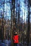 逗人喜爱的可爱的严肃的女孩早期的春天画象有黑发看对照相机和替换者的热围巾和红色夹克的 库存图片