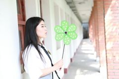 逗人喜爱的可爱的亚洲中国俏丽的女孩穿戴学生衣服在类戏剧的学校与绿色风车 图库摄影