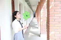 逗人喜爱的可爱的亚洲中国俏丽的女孩穿戴学生衣服在类戏剧的学校与绿色风车 免版税库存照片