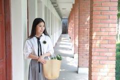 逗人喜爱的可爱的亚洲中国俏丽的女孩穿戴学生衣服在类的学校享受业余时间 免版税库存照片