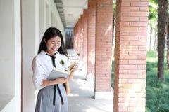 逗人喜爱的可爱的亚洲中国俏丽的女孩穿戴学生衣服在类的学校享用业余时间微笑和阅读书 库存图片