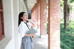 逗人喜爱的可爱的亚洲中国俏丽的女孩穿戴学生衣服在类的学校享用业余时间微笑和阅读书 图库摄影