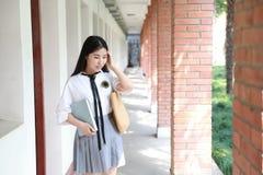 逗人喜爱的可爱的亚洲中国俏丽的女孩穿戴学生衣服在类的学校享用业余时间微笑和阅读书 免版税图库摄影