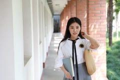 逗人喜爱的可爱的亚洲中国俏丽的女孩穿戴学生衣服在类的学校享用业余时间微笑和阅读书 库存照片