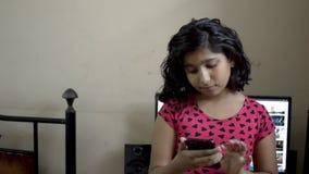 逗人喜爱的可爱的印度亚裔白种人愉快的女孩孩子繁忙在手机短信的读书正面图画象 影视素材