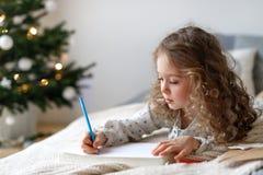 逗人喜爱的可爱的卷曲矮小的女孩在舒适的床上说谎在她的有装饰的杉树的卧室在背景中 免版税库存图片