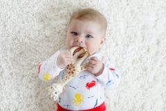 逗人喜爱的可爱的新出生的小孩子画象有玩具的 免版税库存图片