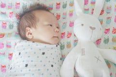 逗人喜爱的可爱的新出生的男婴在毯子包裹了或包扎,睡觉,并且两只眼睛在孩子床上某时打开 库存照片