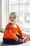 逗人喜爱的可爱的白种人男婴画象坐windowsi 免版税图库摄影