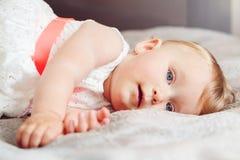 逗人喜爱的可爱的白肤金发的白种人微笑的小儿童女孩画象有蓝眼睛的在有说谎在床上的红色弓的白色礼服 免版税库存照片