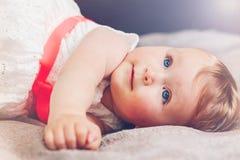 逗人喜爱的可爱的白肤金发的白种人微笑的小儿童女孩画象有蓝眼睛的在有说谎在床上的红色弓的白色礼服 库存图片