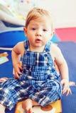 逗人喜爱的可爱的白肤金发的白种人微笑的男婴画象有棕色眼睛的在蓝色连裤外衣坐地板在孩子屋子里 免版税库存图片