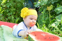 逗人喜爱的可爱的蓝眼睛女婴6个月去掉一半西瓜 在叶子背景  晴朗的日 库存图片
