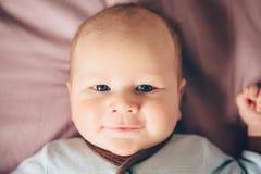 逗人喜爱的可爱的滑稽的白白种人白肤金发的矮小的男婴特写镜头画象新出生与说谎在床上的蓝眼睛 免版税库存照片