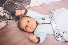 逗人喜爱的可爱的滑稽的白白种人白肤金发的矮小的男婴画象新出生与蓝灰色注视说谎在大父母床上 免版税库存图片