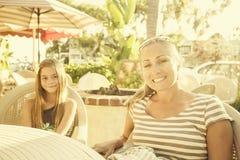 逗人喜爱的吃在一个室外咖啡馆的女孩和她的母亲 库存图片