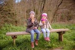 逗人喜爱的吃松饼的男孩和小女孩坐  库存照片