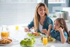 逗人喜爱的吃沙拉的母亲和女儿在桌上 免版税库存照片