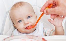 逗人喜爱的吃的男婴 免版税库存图片